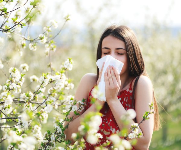 Allergy season, young woman blowing her nose and sneezing in blossoming garden.